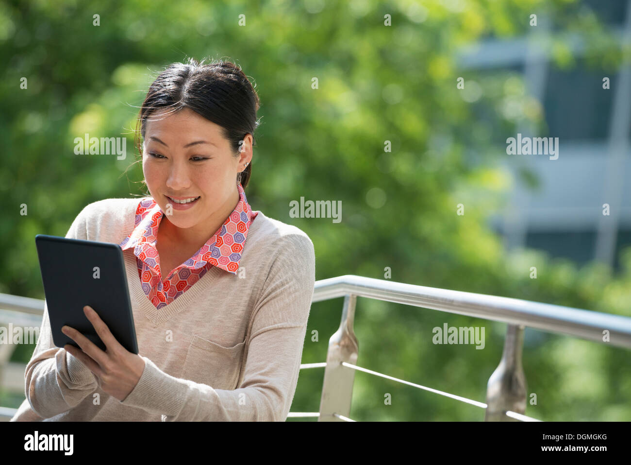 Summer. Business people. A woman using a digital tablet, working. Keeping in touch. - Stock Image