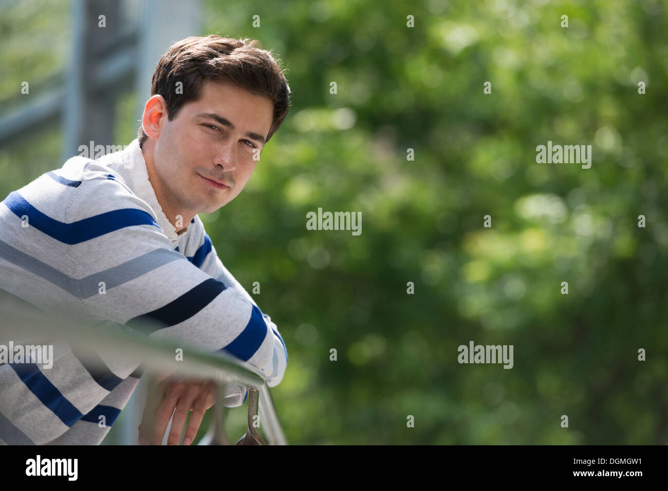 Summer. Business people. A man leaning on a railing relaxing. Off grid. - Stock Image
