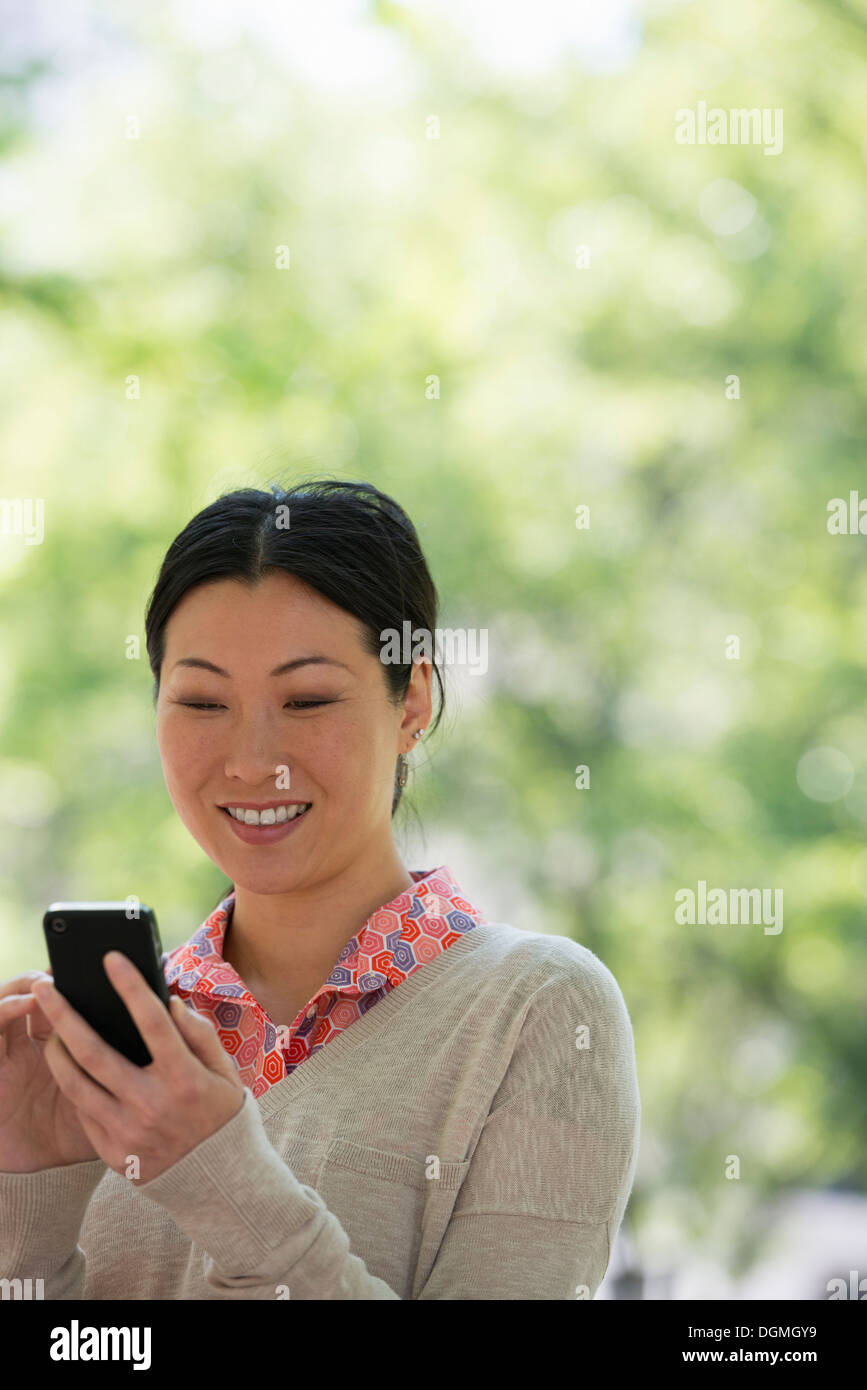 Summer. Business people. A woman checking her smart phone for messages. - Stock Image