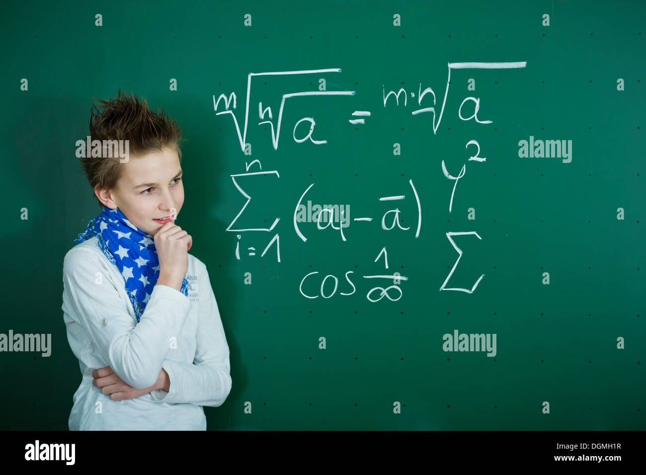 Schoolboy pondering a mathematical formula on a school blackboard, Germany - Stock Image