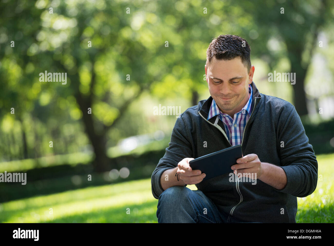 Summer. Business people. A man sitting using a digital tablet, keeping in touch. Stock Photo