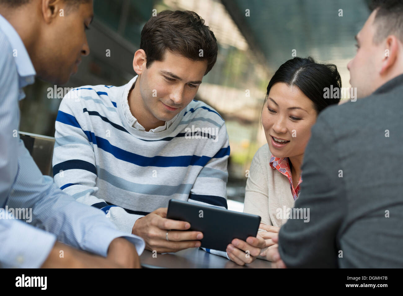Business people on the move. Four people gathered around a digital tablet having a discussion. - Stock Image