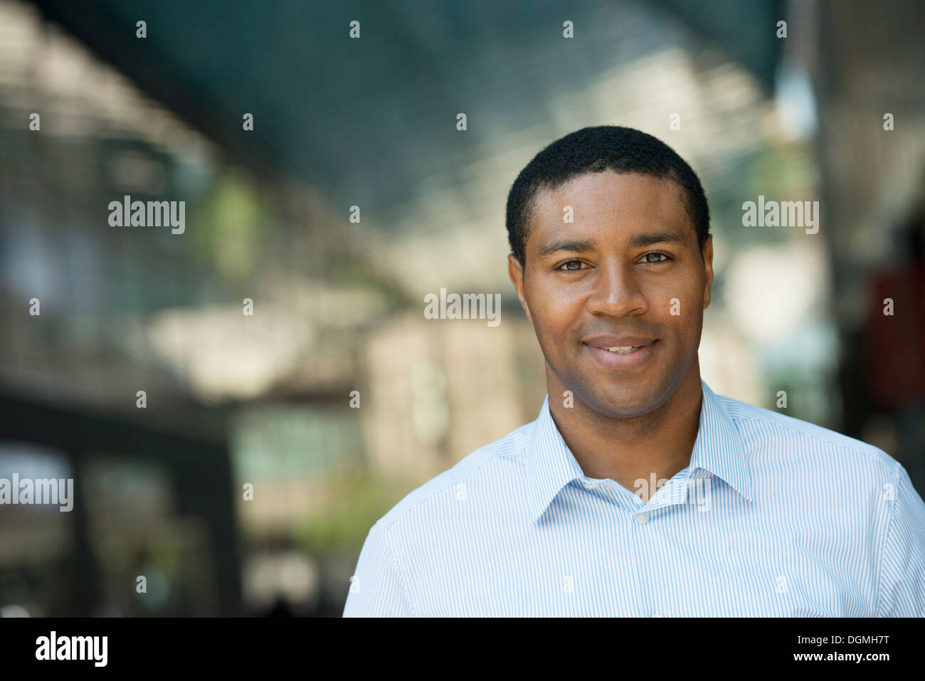 Business people on the move. A man in an open necked shirt smiling. - Stock Image