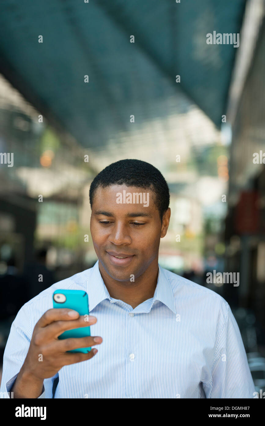 Business people on the move. A man in an open necked shirt checking his phone. - Stock Image