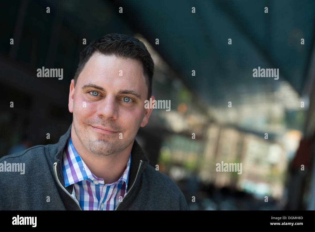 Business people on the move. A man in a open necked shirt and jacket. - Stock Image