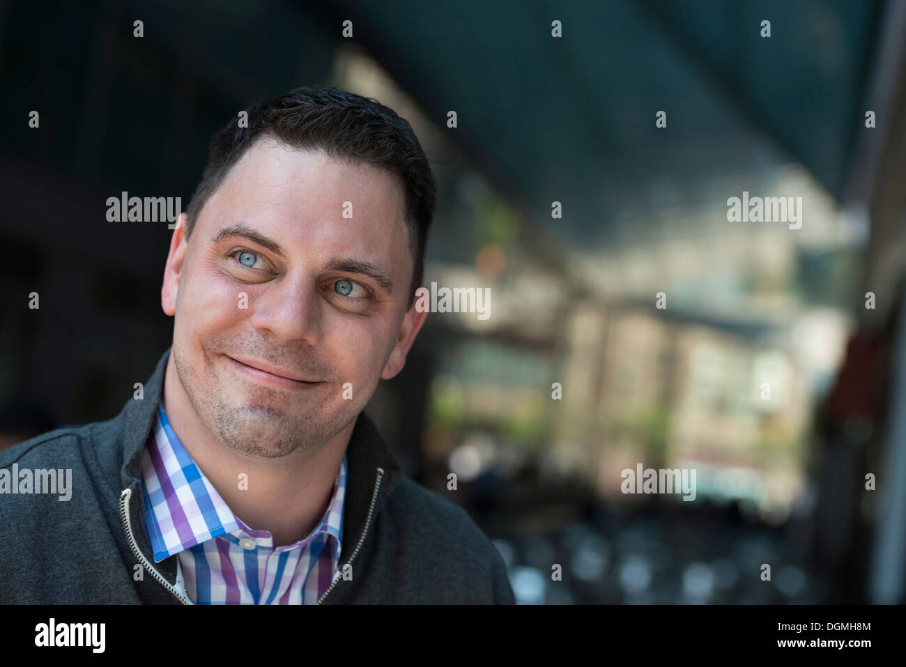 Business people on the move. A man in a open necked shirt and jacket. Stock Photo