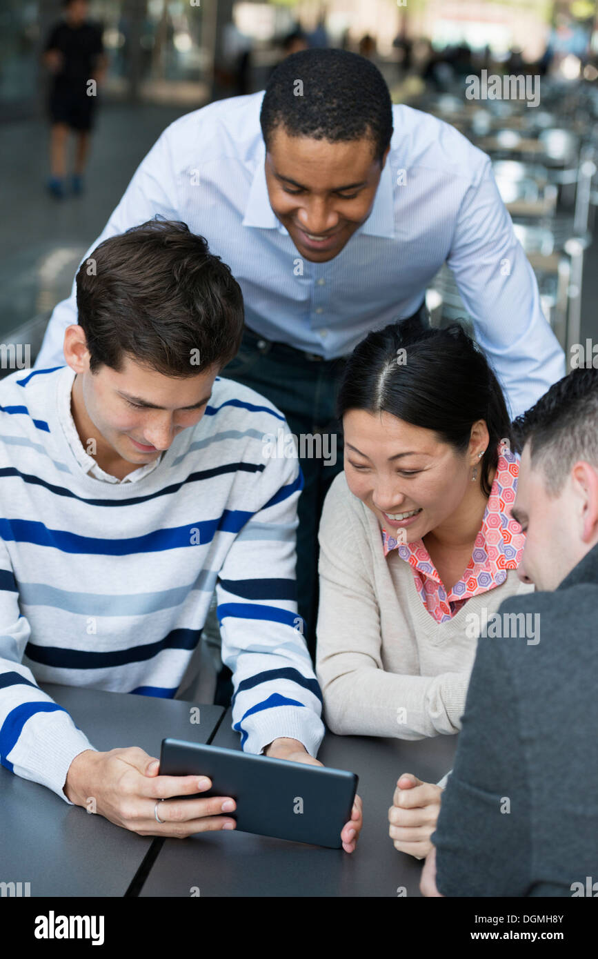 Business people on the move. Four people gathered around a digital tablet having a discussion. Overhead view. - Stock Image