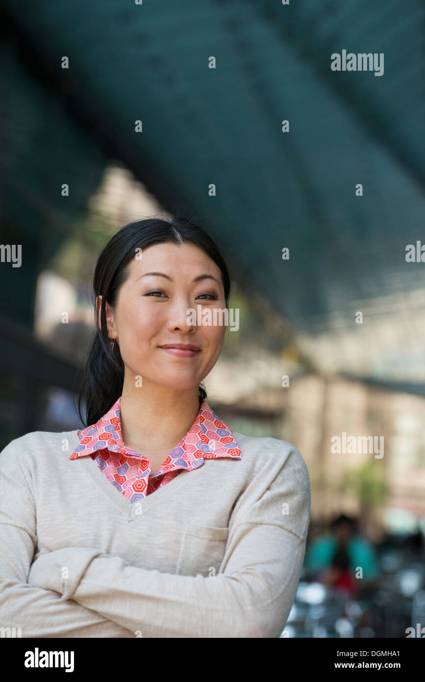 Business people on the move. A woman in a pink shirt and beige sweater. - Stock Image
