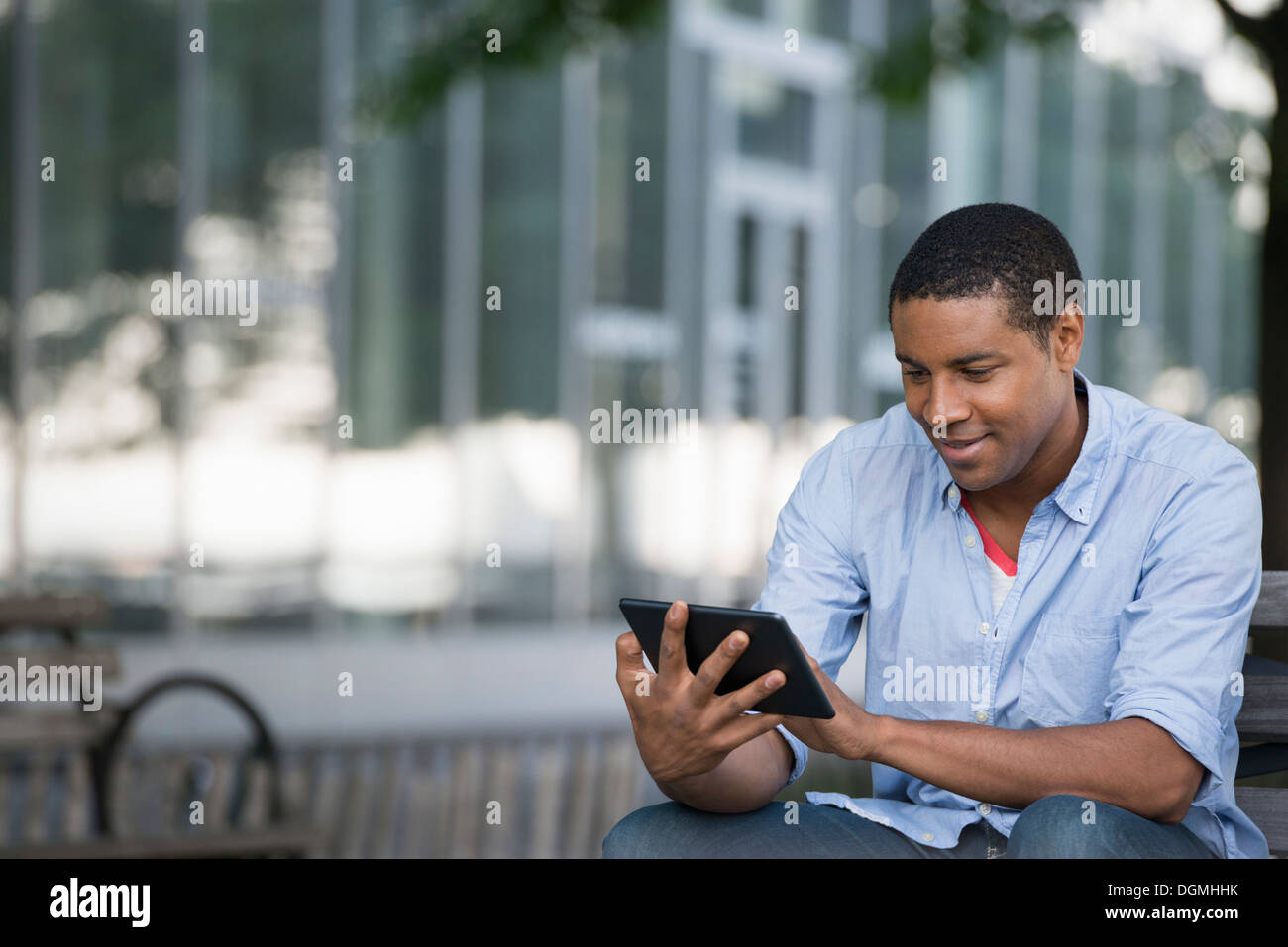 Summer in the city. People outdoors, keeping in touch while on the move. A man sitting on a bench using a digital tablet. - Stock Image