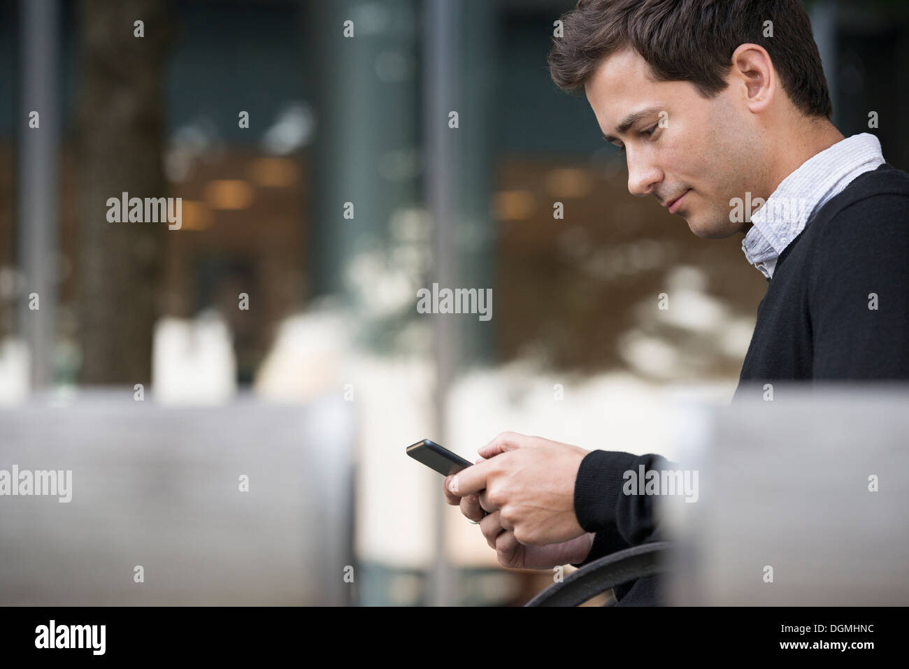 Summer in the city. A man sitting on a bench using a smart phone. - Stock Image