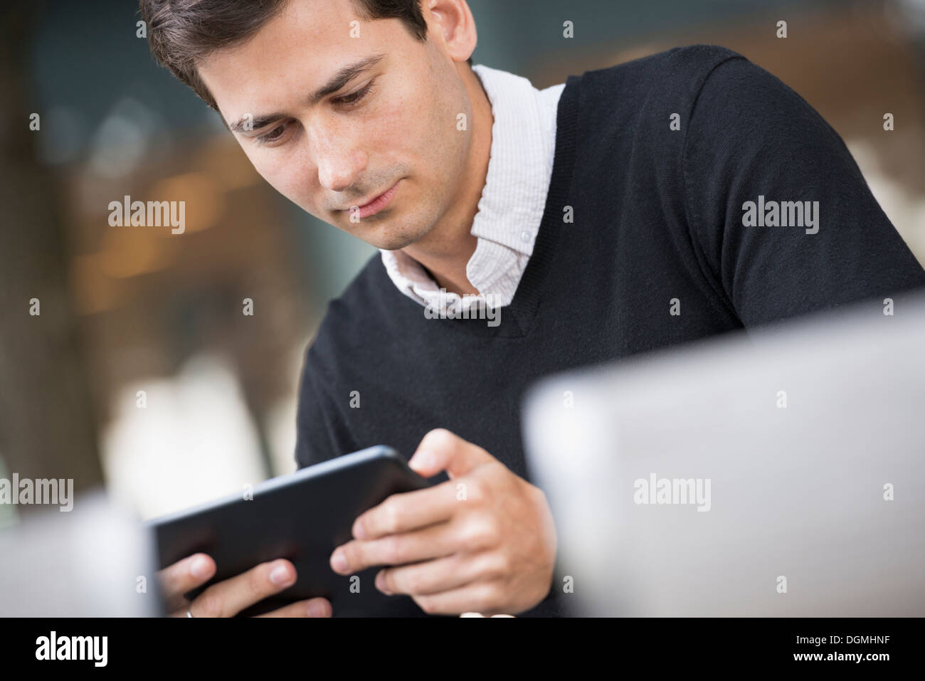 Summer in the city. A man sitting on a bench using a digital tablet. - Stock Image