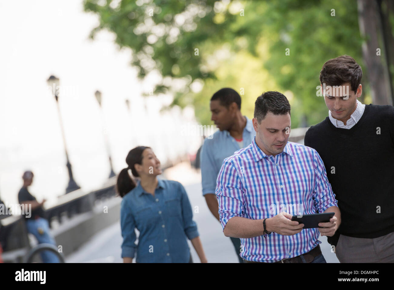Summer in the city. Four people in a group. One using his digital tablet. Stock Photo
