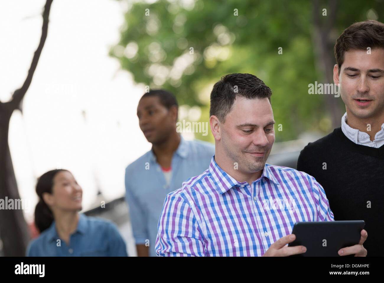Summer in the city. Four people in a group. One using his digital tablet. - Stock Image