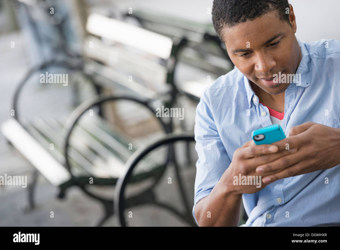 Summer in the city. A man sitting on a bench using a smart phone. Stock Photo