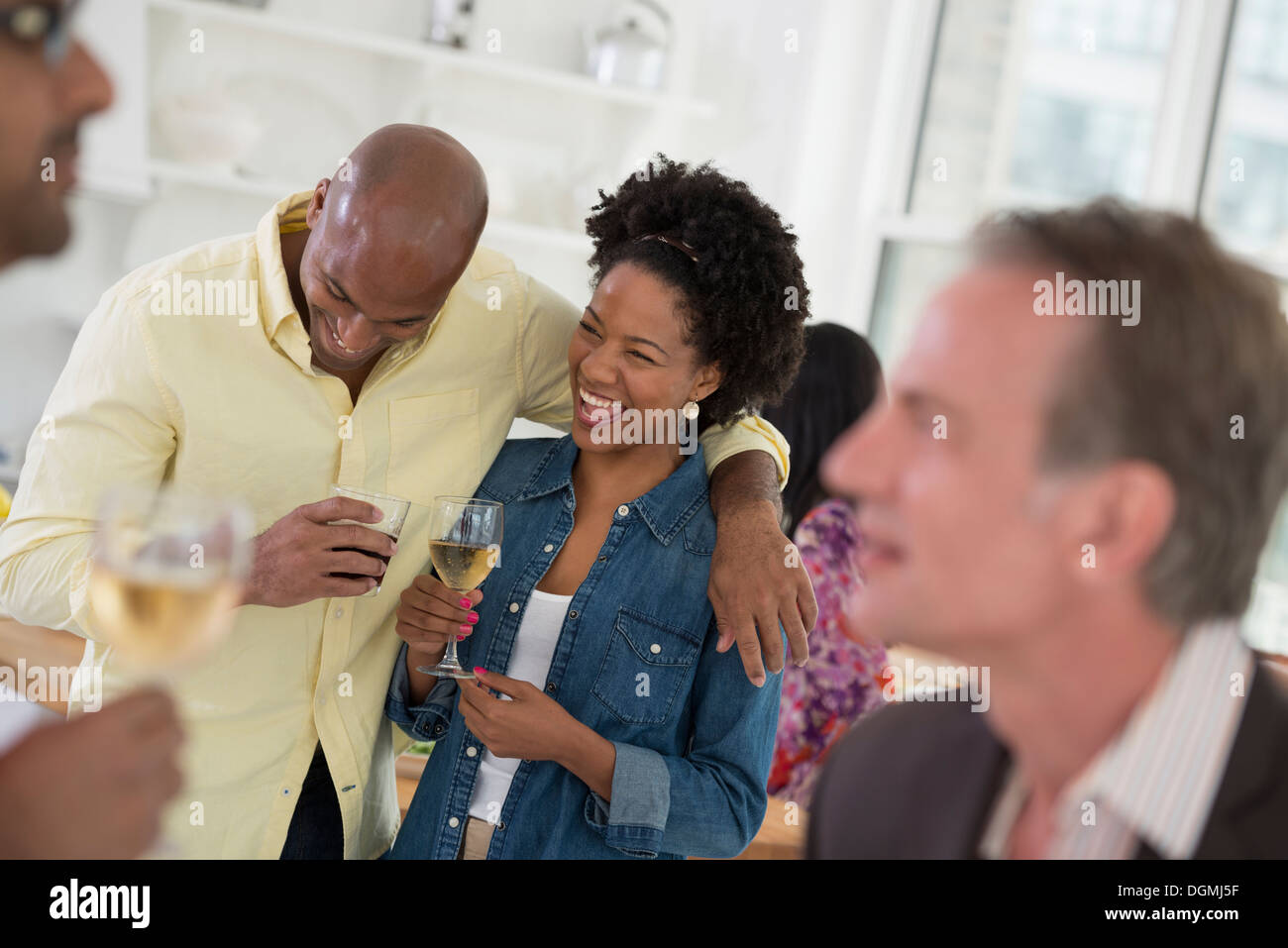 Networking party or informal event. A man and woman, with a crowd around them. - Stock Image