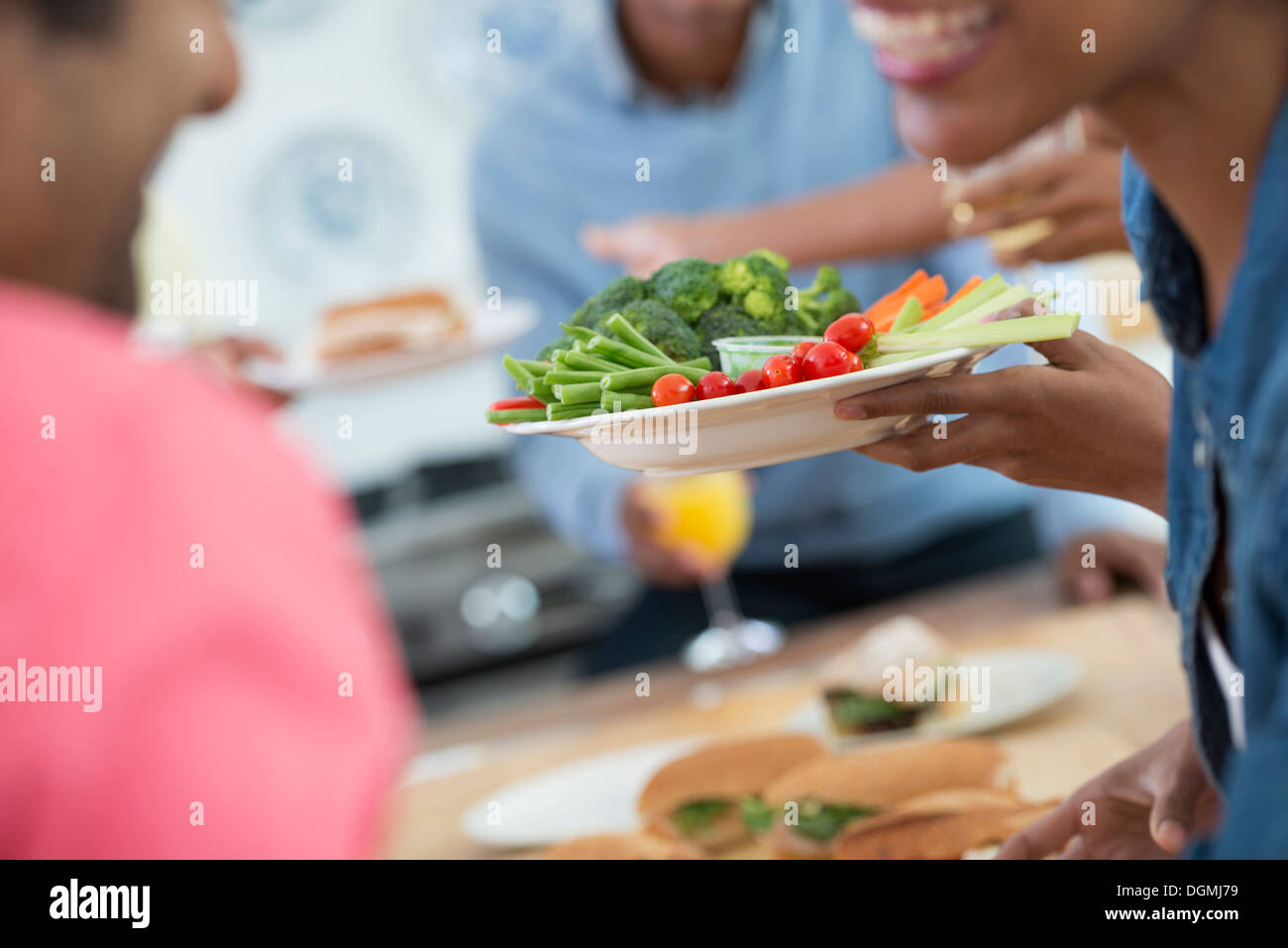 An informal office event. People handing plates of food across a buffet table. - Stock Image