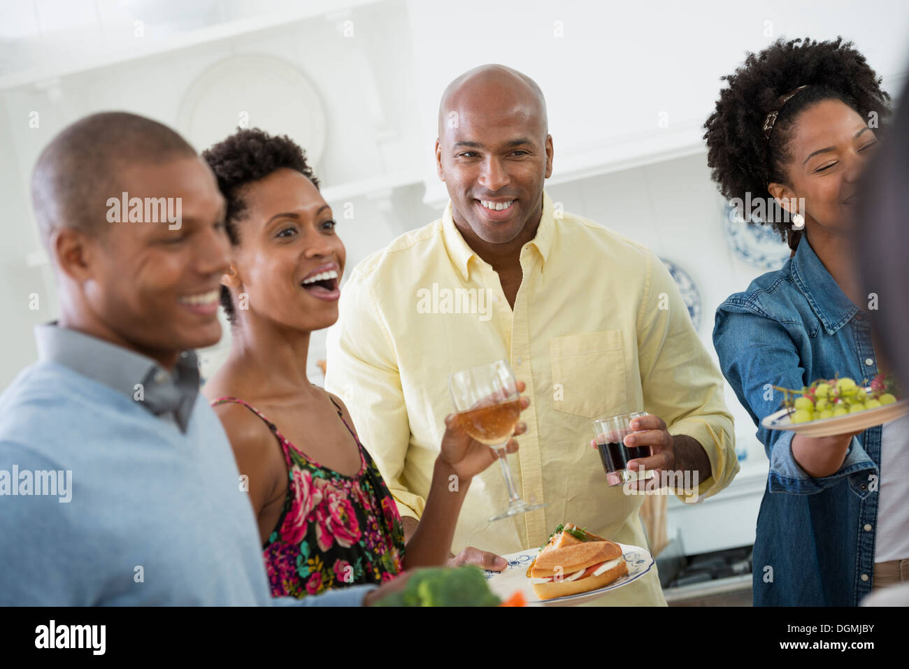 An informal office party. People handing plates of food across a buffet table. - Stock Image