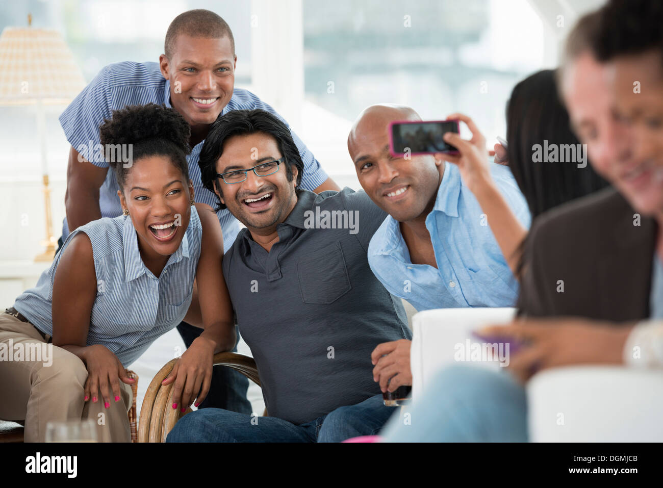 office event. A man taking a selfie of the group with a smart phone. - Stock Image