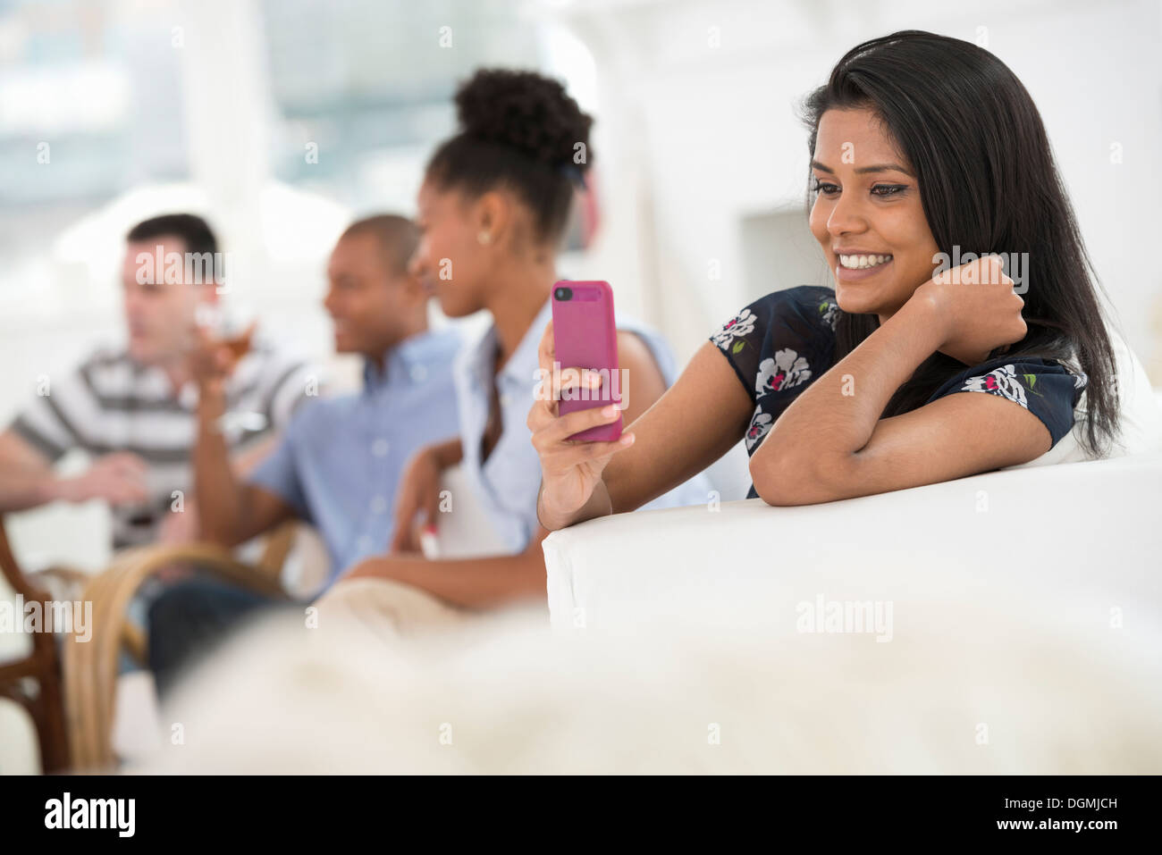 Office event. A woman using her pink smart phone. - Stock Image
