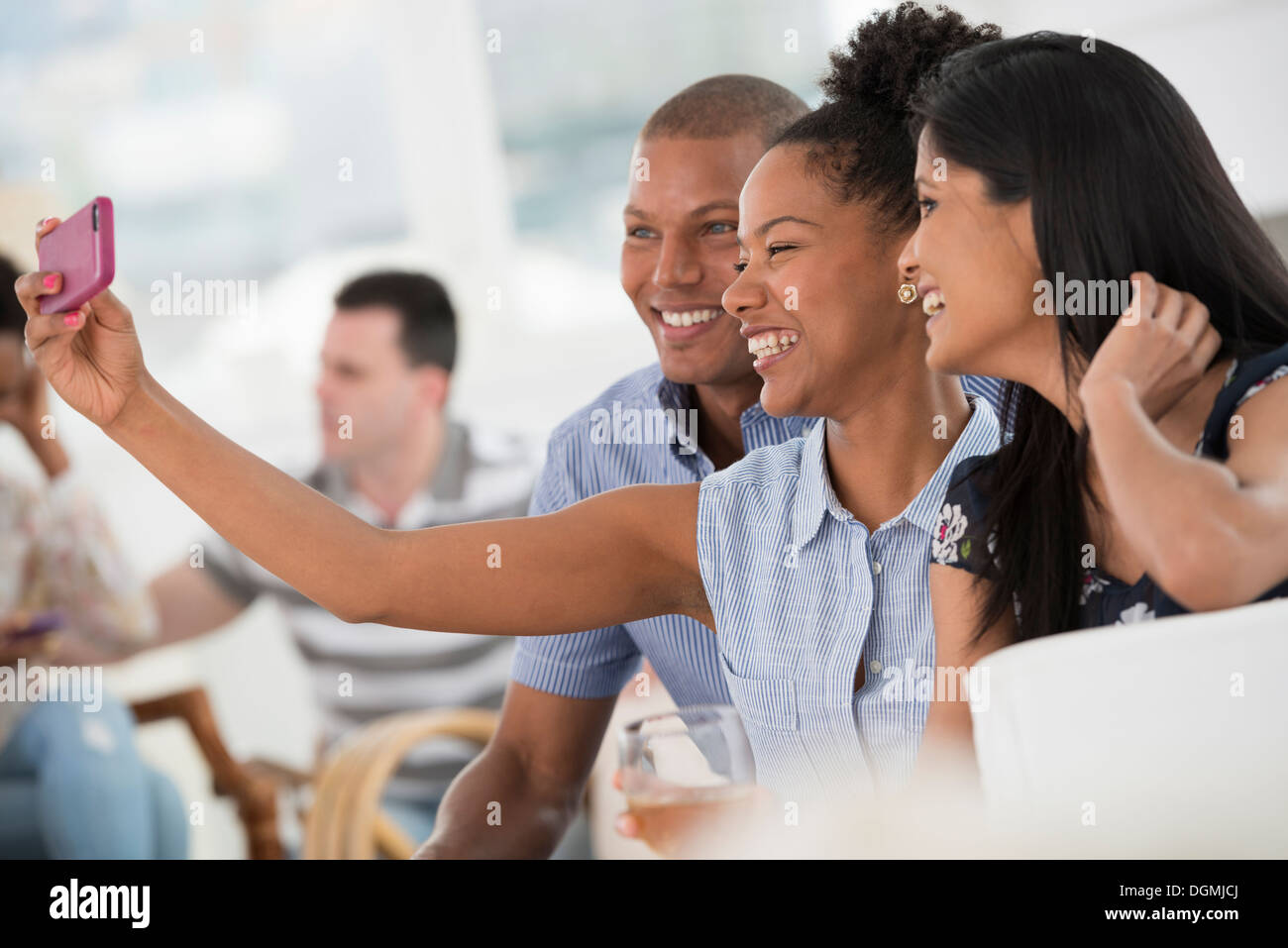 Office event. A woman taking a selfie of the group with a smart phone. - Stock Image