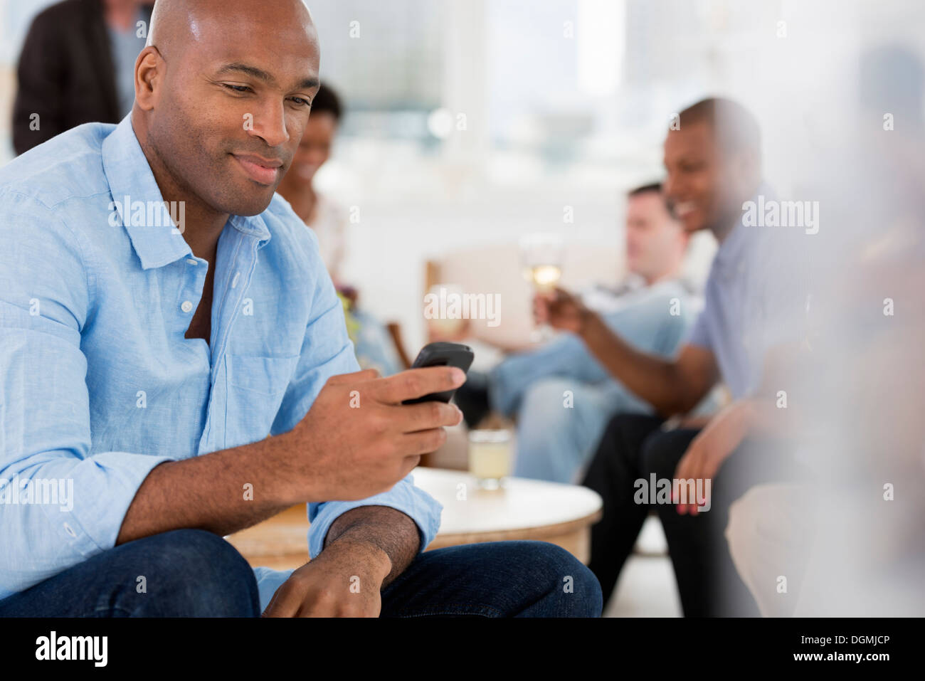 Office event. A man using his smart phone. - Stock Image