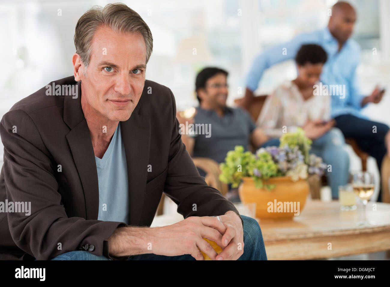 Office event. A man seated away from the group. - Stock Image
