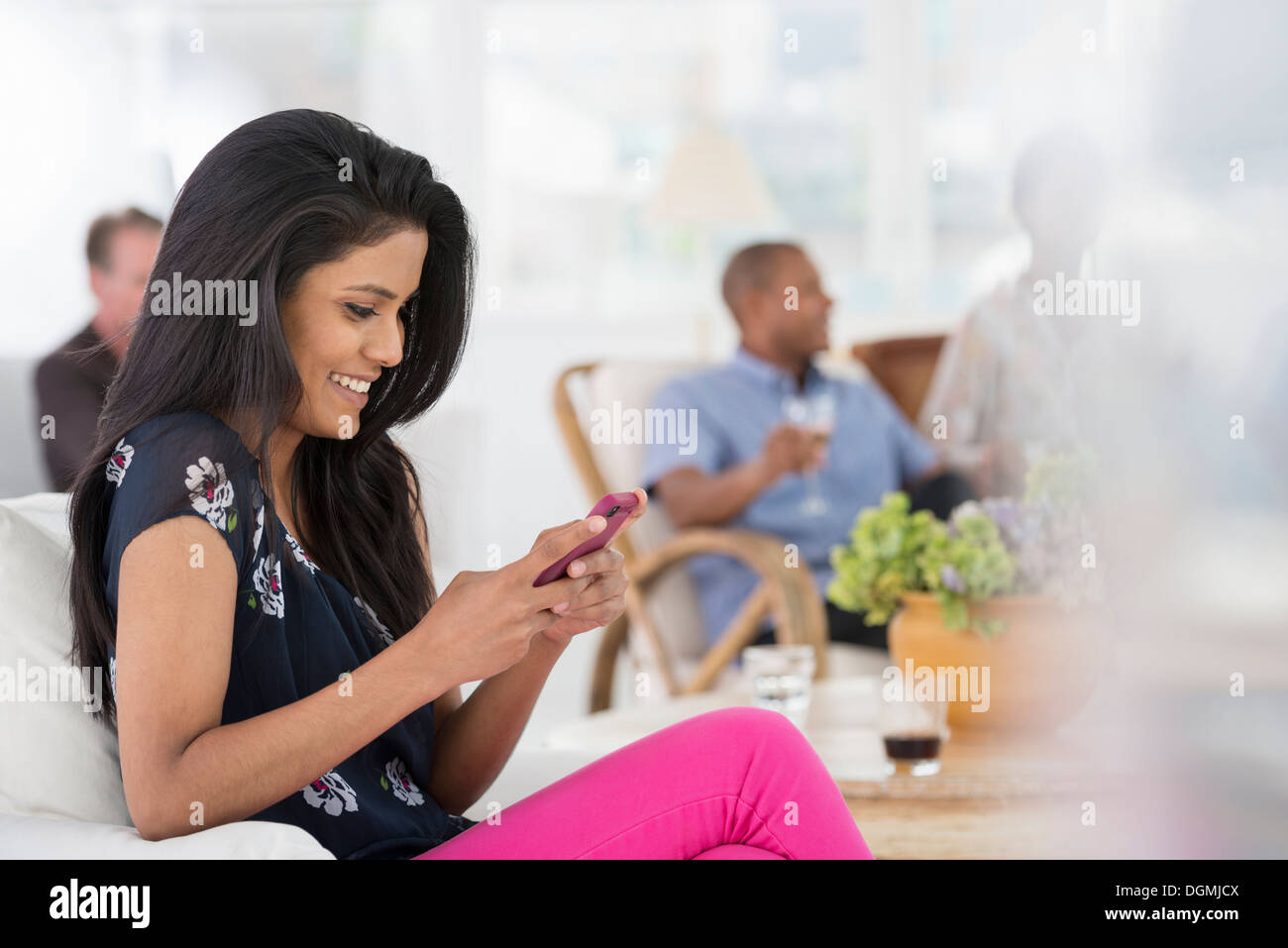 Office event. A woman seated on the sofa using her smart phone. - Stock Image