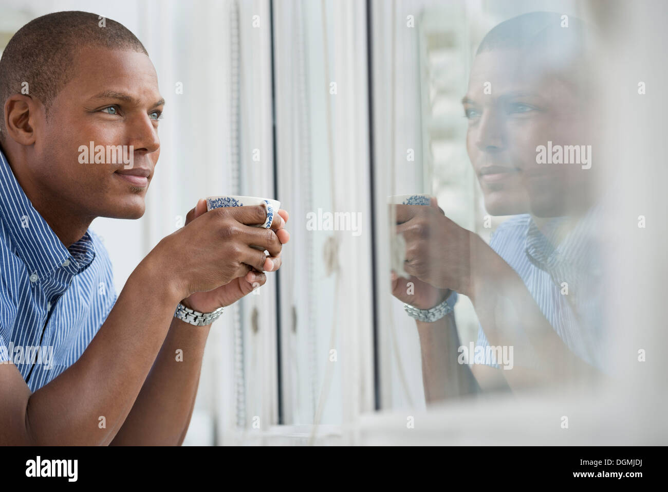 Office. A young man leaning on the windowsill holding a cup of tea. - Stock Image