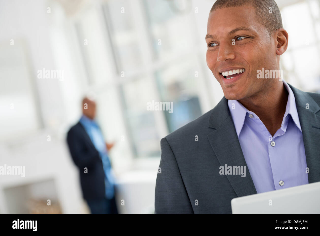 Business people. A young man in a suit using a digital tablet. - Stock Image