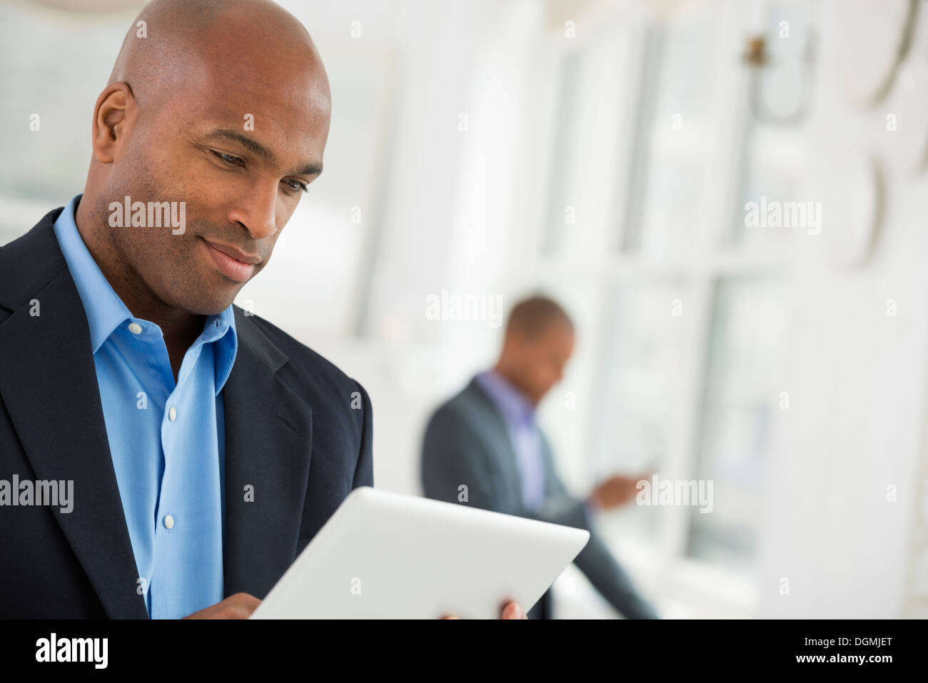 Business people. A man in a business suit using a digital tablet. - Stock Image