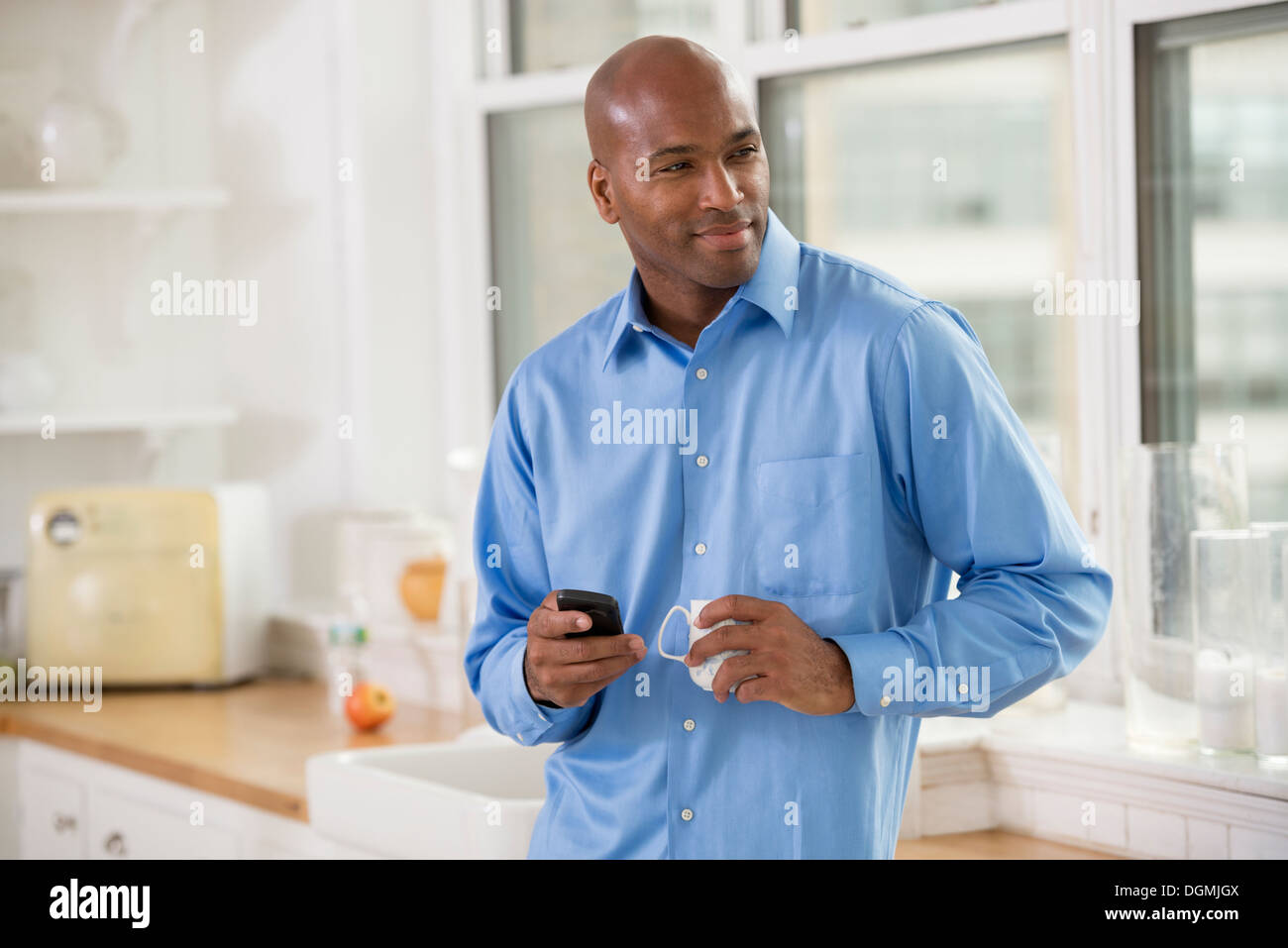 Business people. A man in a blue shirt, with a smart phone in his hand. - Stock Image