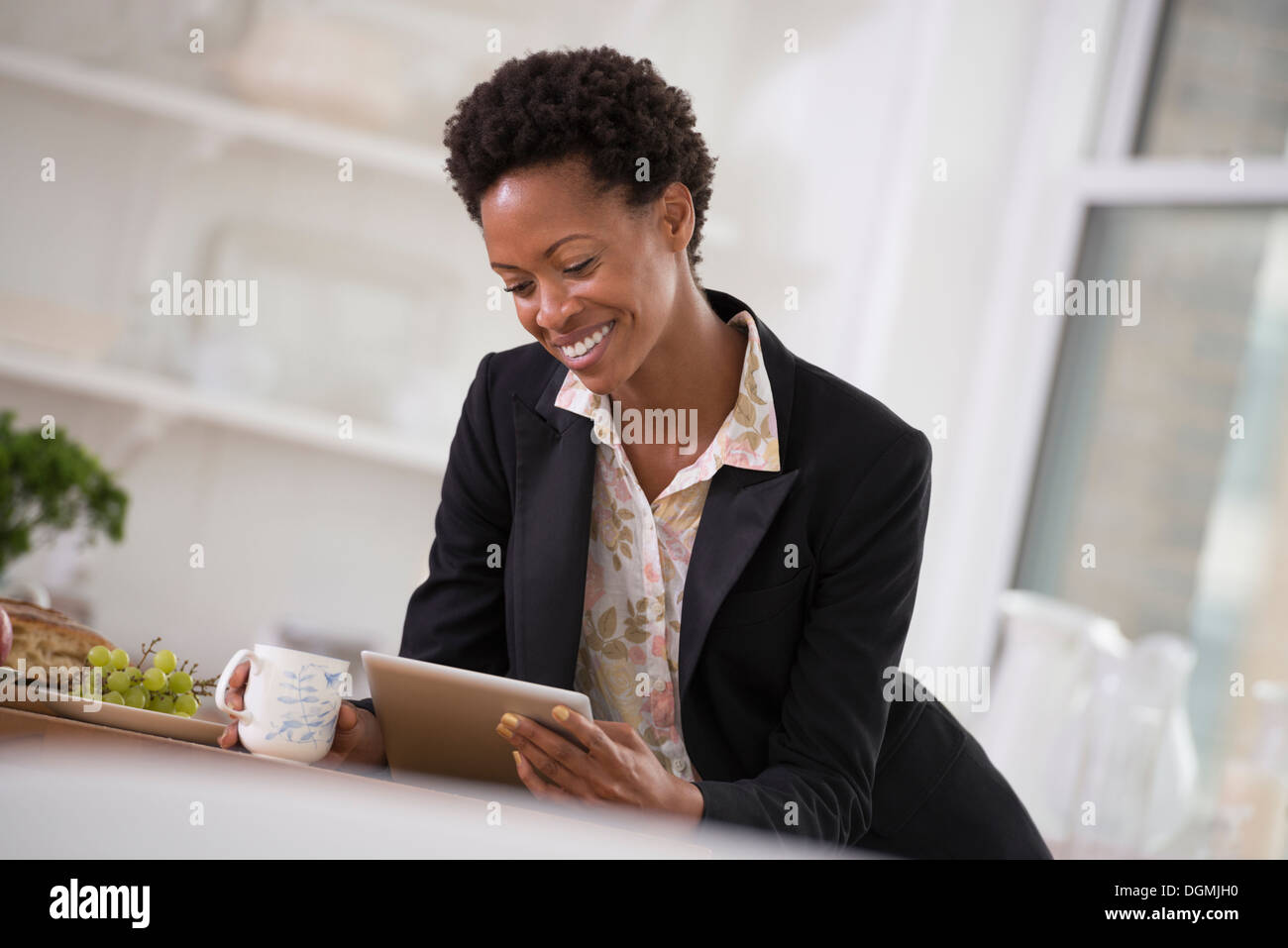 Business people. A woman in a black jacket using a digital tablet. Stock Photo