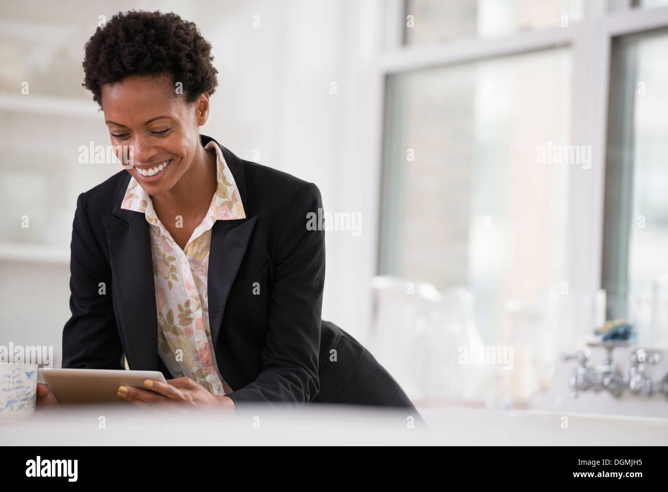 Business people. A woman in a black jacket using a digital tablet. - Stock Image