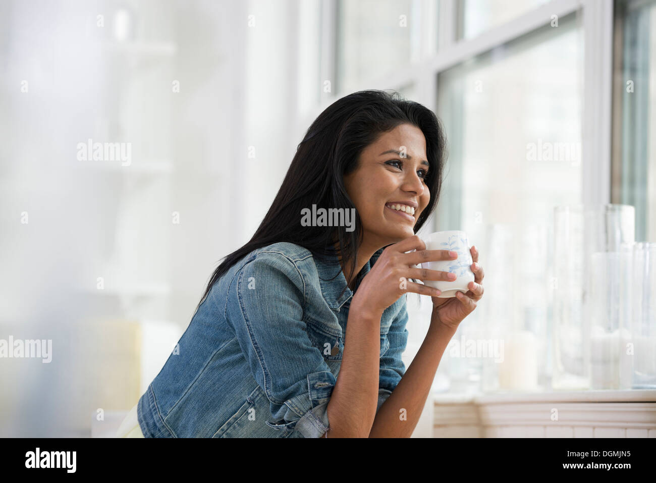 A young woman wearing a denim shirt, holding a china cup. - Stock Image