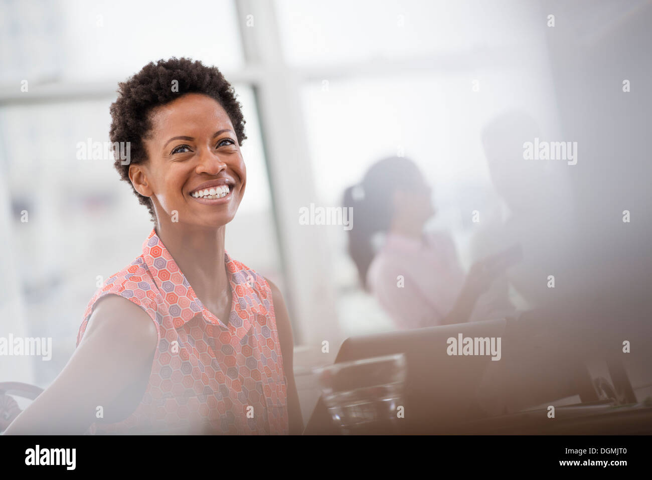 Office life. A young woman in a pink shirt laughing. - Stock Image