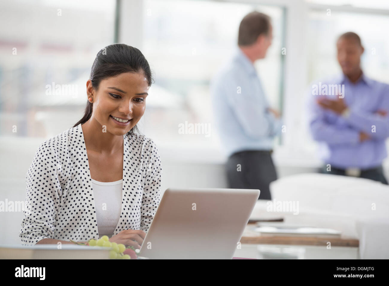 Office life. A woman sitting at a desk using a laptop computer. Two men in the background. - Stock Image
