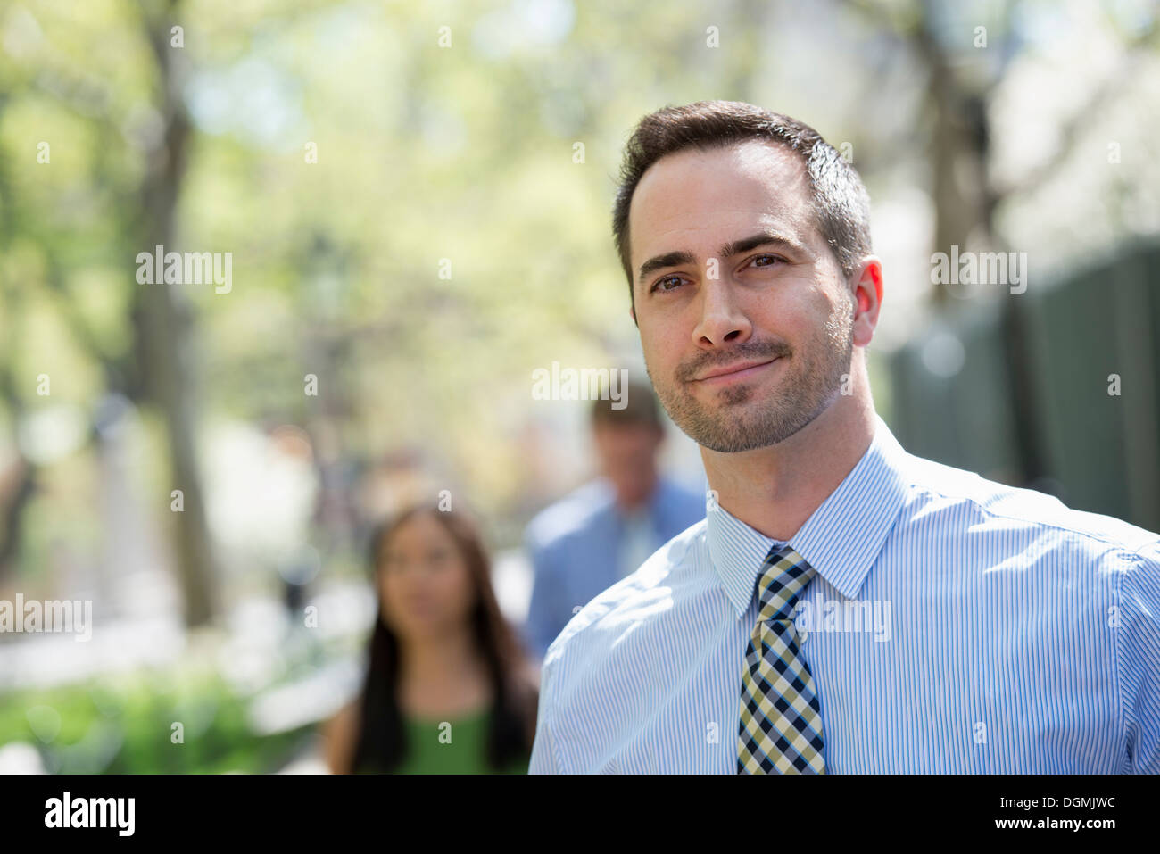 A small group of people, a businesswoman and two businessmen outdoors in the city. - Stock Image