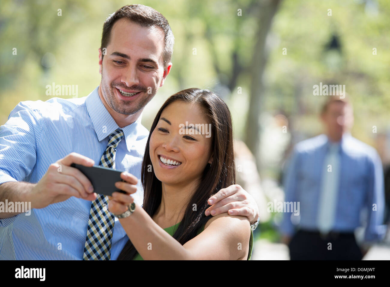 A couple with a smart phone, side by side. A man in the background. - Stock Image