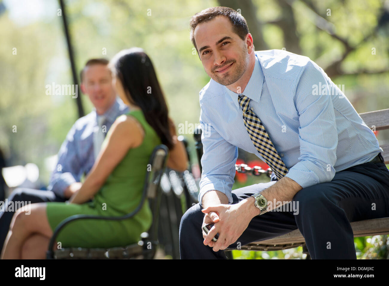 A businesswoman and two businessmen outdoors in the city. Stock Photo