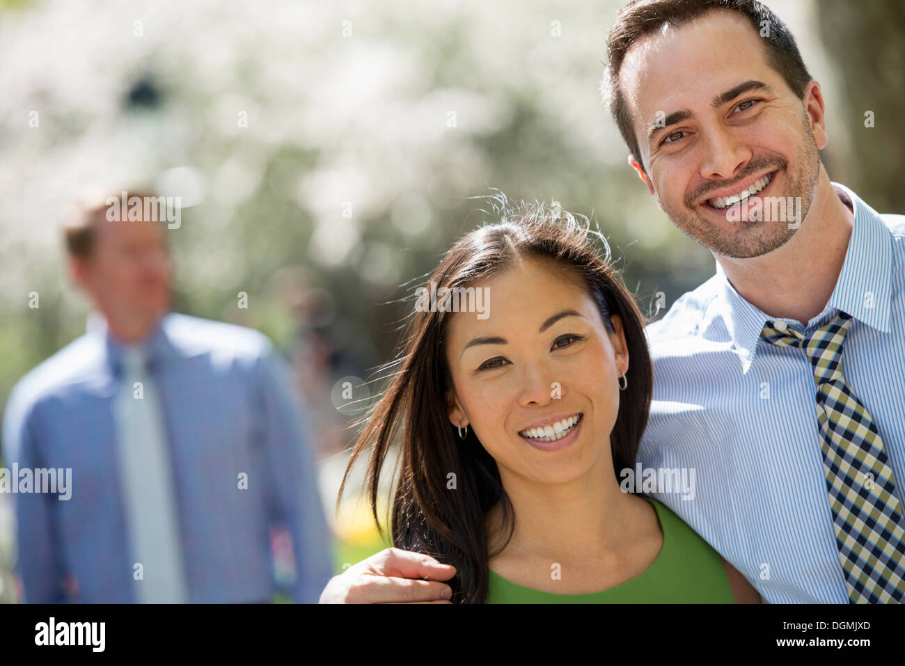 Three people in business dress. A couple side by side smiling at the camera. A man in the background. - Stock Image