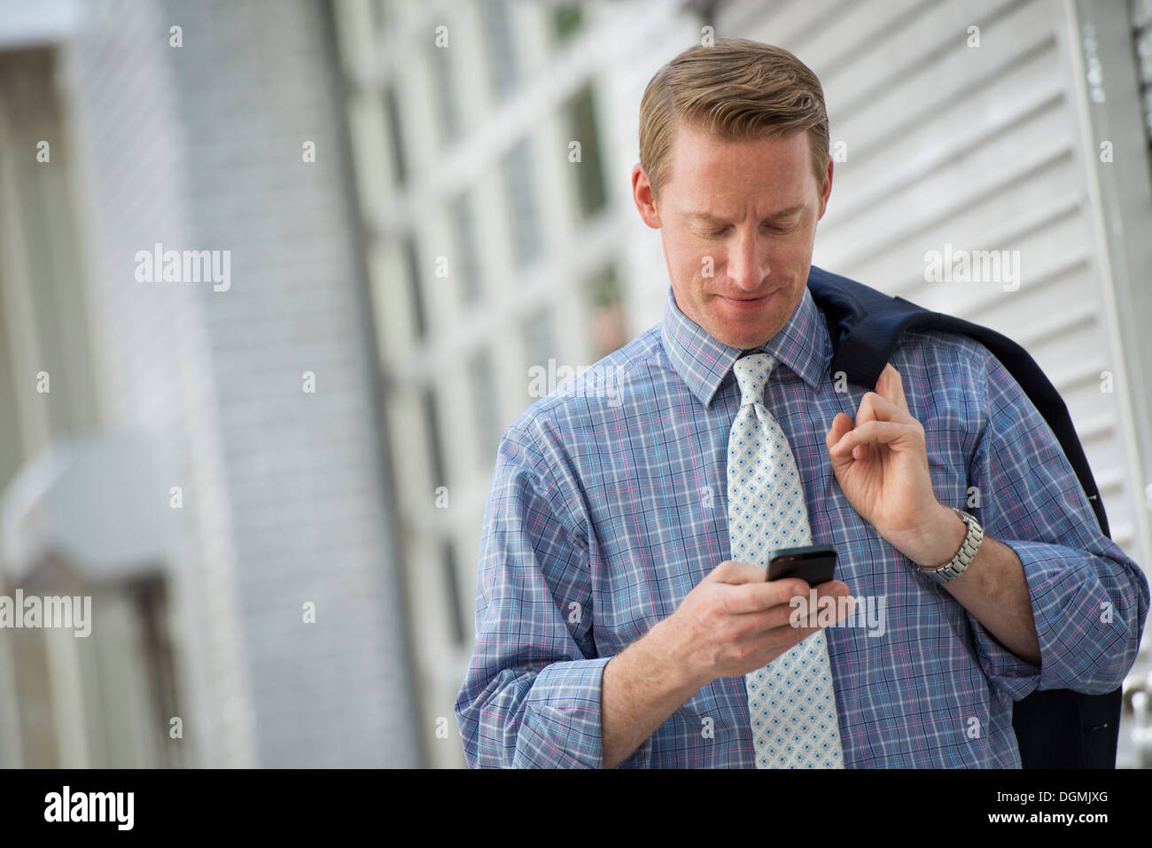 A man with his jacket slung over his shoulder, checking his phone. - Stock Image
