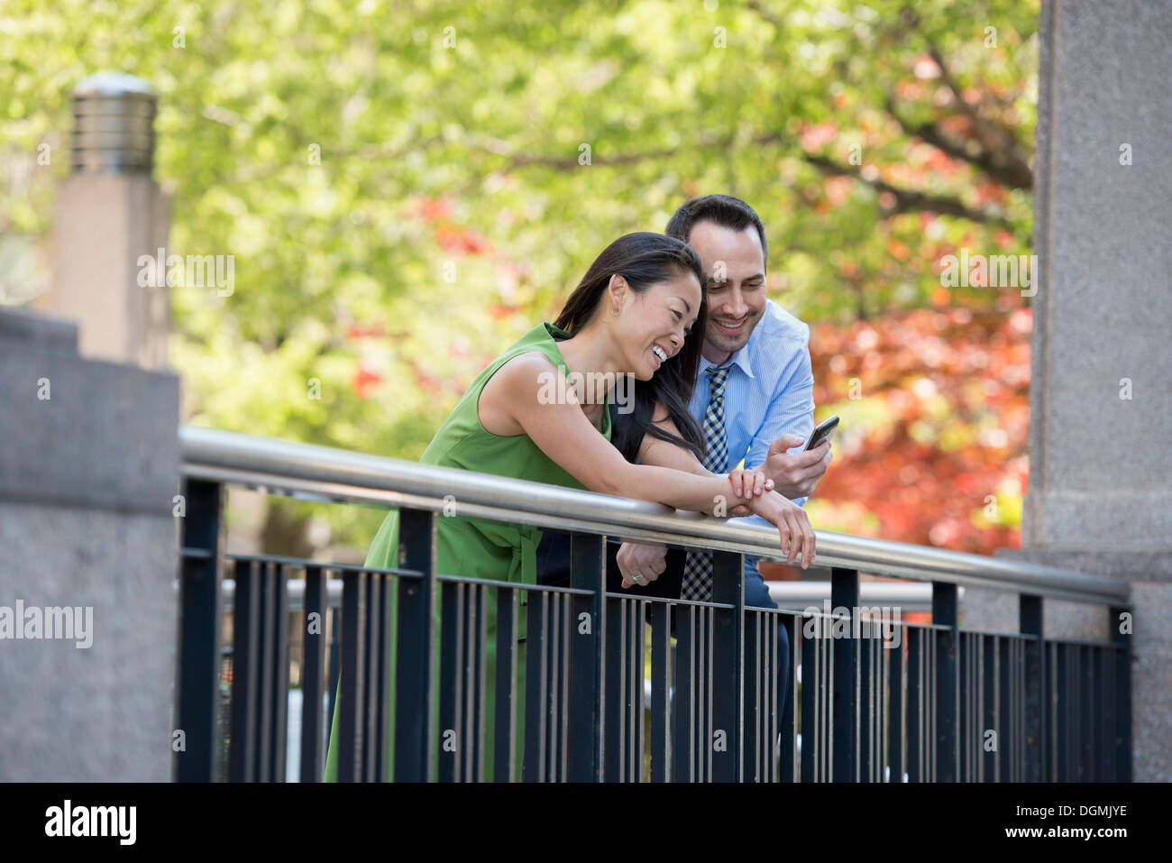 A couple, man and woman checking a smart phone, under the shade of trees in the park. - Stock Image