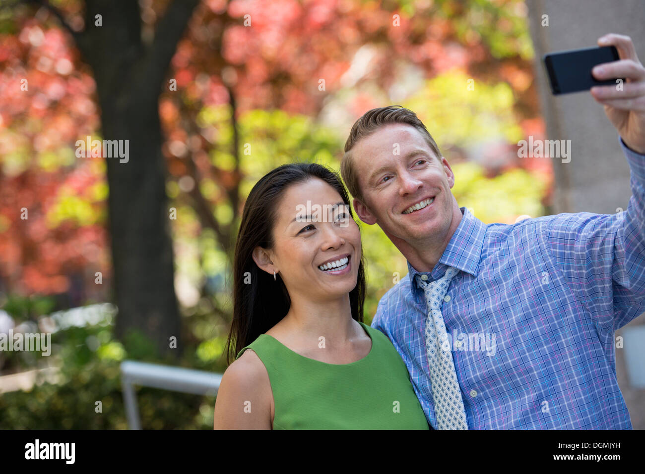 A businesswoman and two businessmen outdoors in the city. - Stock Image