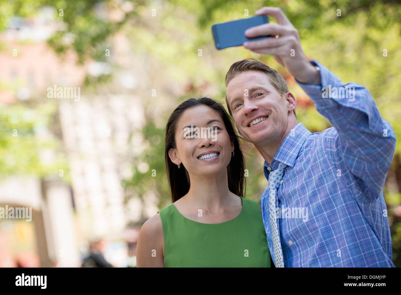A couple, a man and woman taking a selfy with a smart phone. - Stock Image