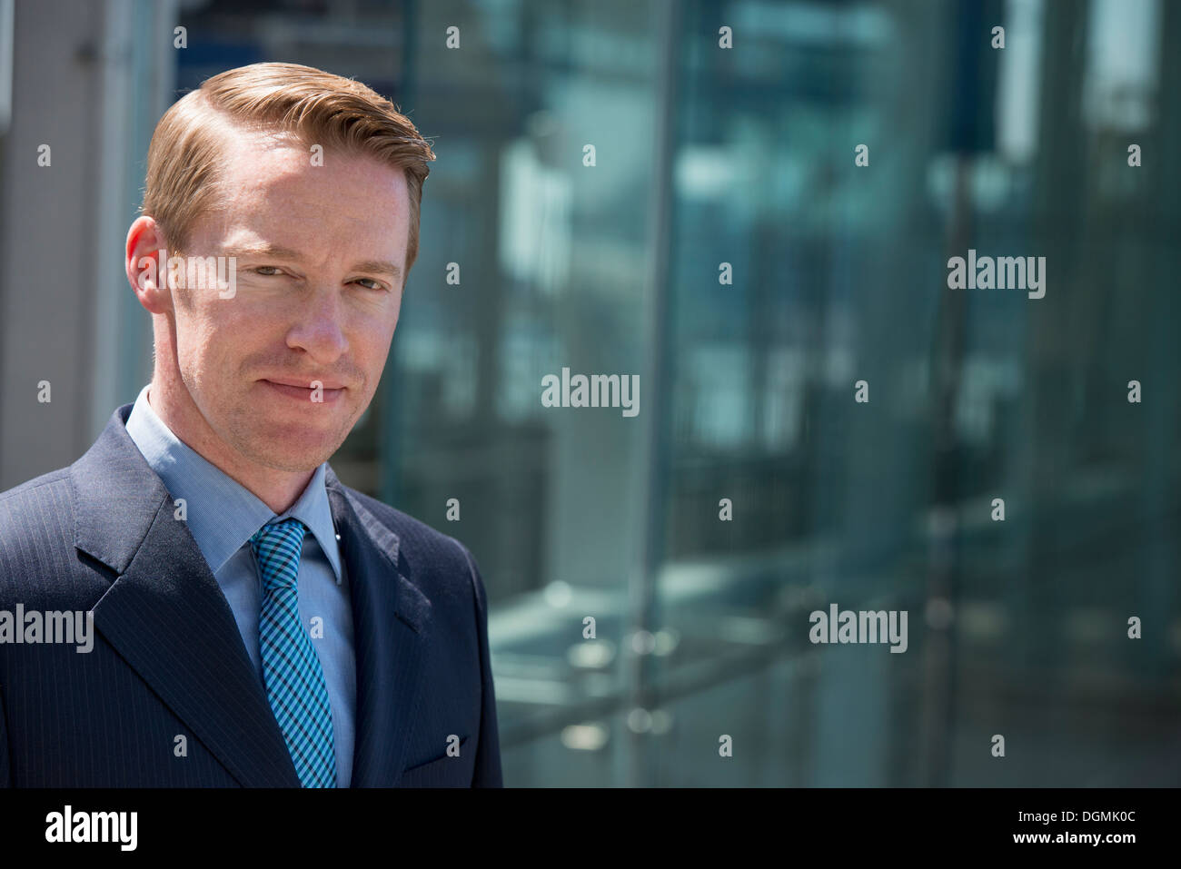 A man in a business suit outside a building with a glass exterior. - Stock Image
