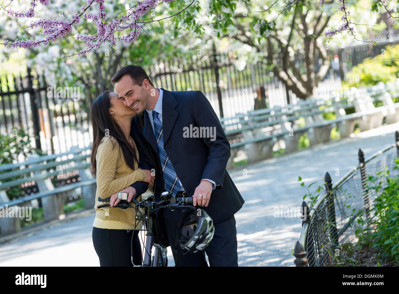 A man in a business suit astride a bicycle. A woman kissing him goodbye. - Stock Image