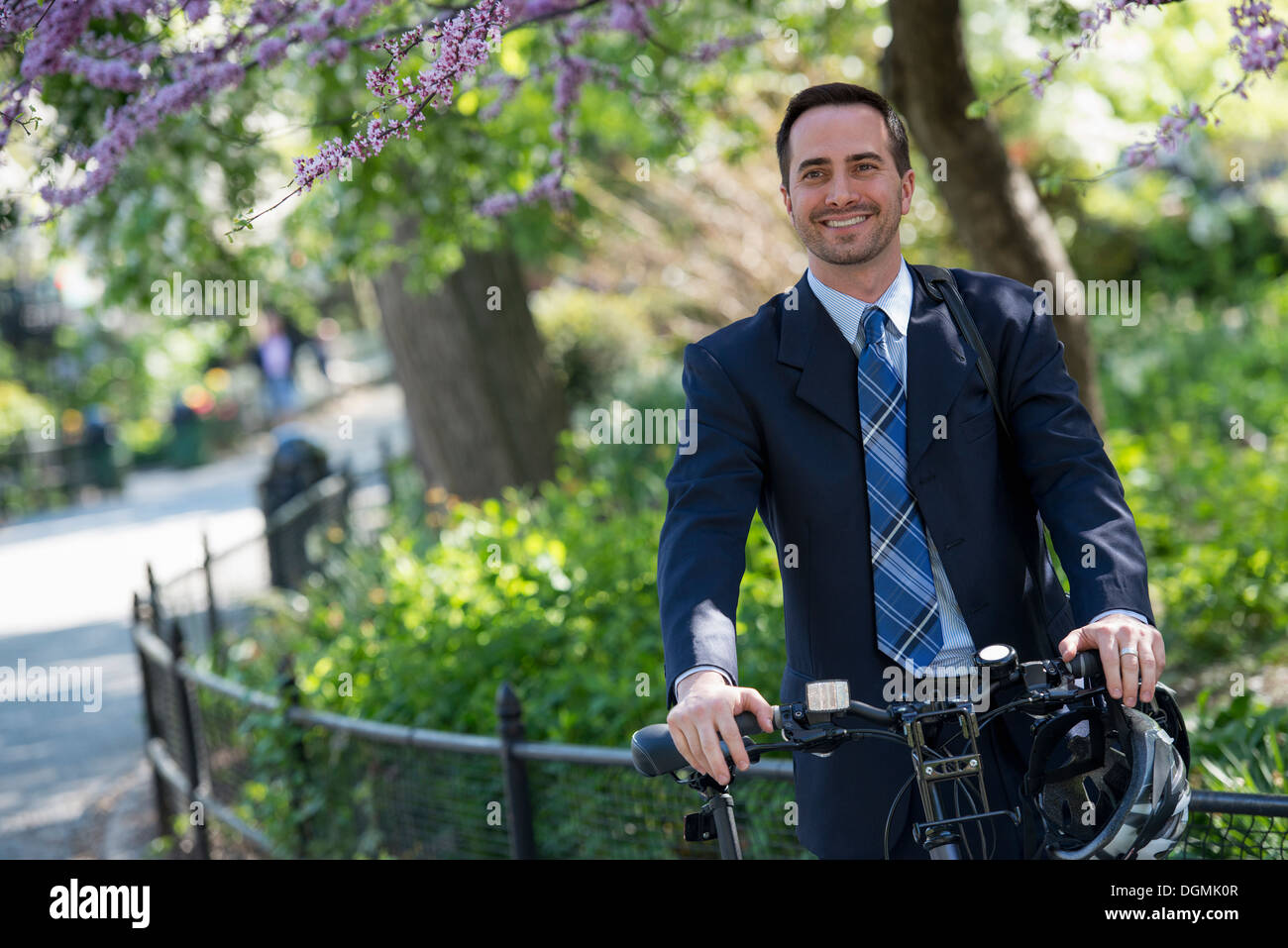 A man in a business suit astride a bicycle with helmet in hand. - Stock Image