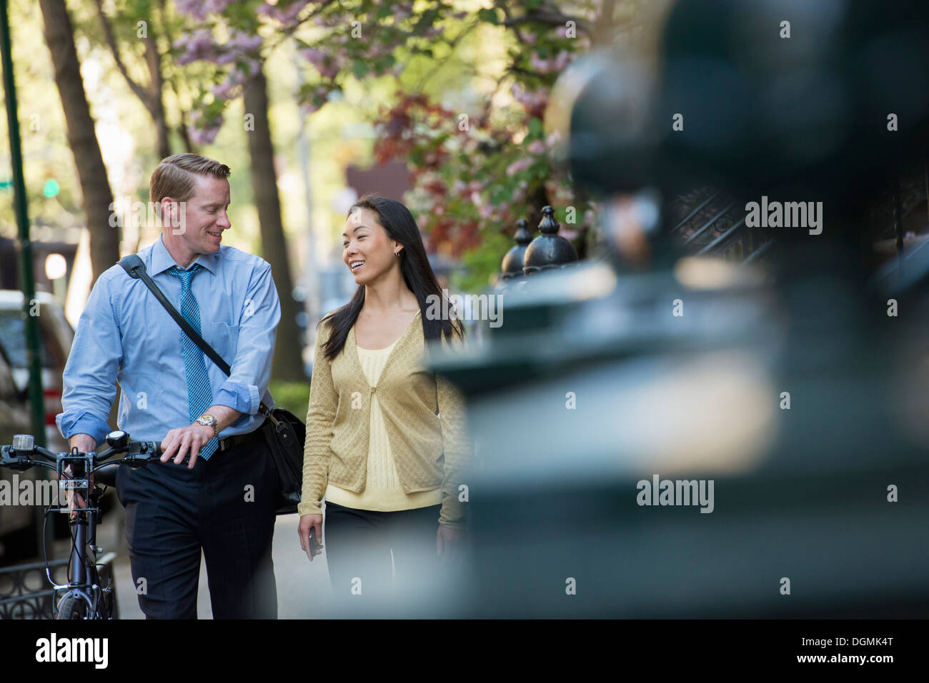 A man in a shirt and tie pushing a bicycle, and talking to a woman. - Stock Image