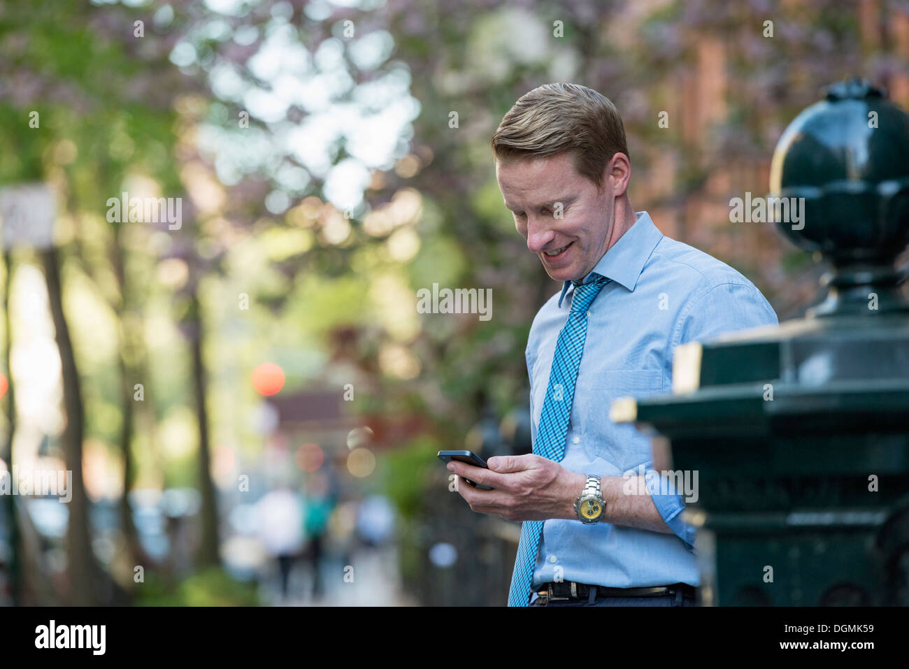 A man in a business shirt and tie, looking down and checking his phone. - Stock Image