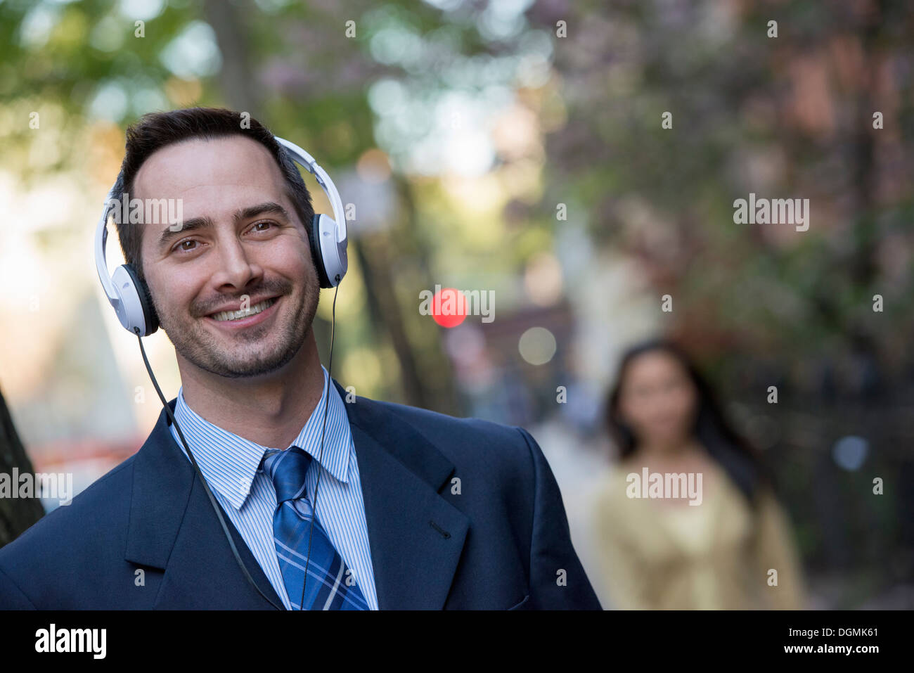 A man in a business suit wearing white headphones, listening to music. - Stock Image